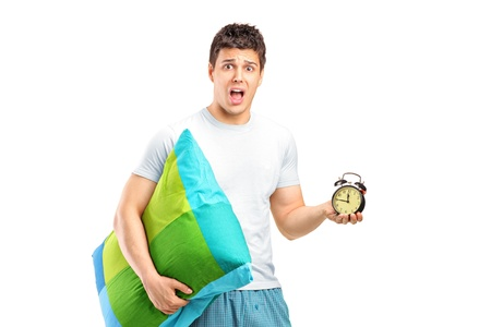 Portrait of a shocked male holding a pillow and alarm clock isolated on white background Stock Photo - 13166955