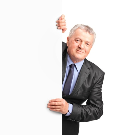 Smiling mature businessman holding a white panel and gesturing isolated on white background photo