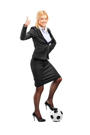 high heeled: Full length portrait of a woman in high heels standing on a soccer ball and giving thumb up isolated on white background Stock Photo