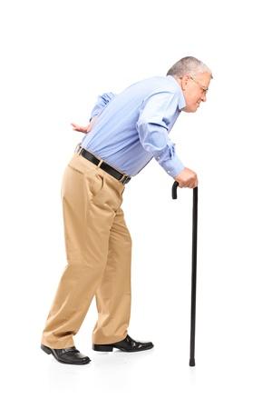 dolor de espalda: Retrato de cuerpo entero de un hombre mayor caminando con bast�n sobre fondo blanco Foto de archivo