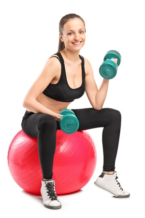 Smiling female lifting up a dumbbells seated on a fitness ball isolated on white background photo