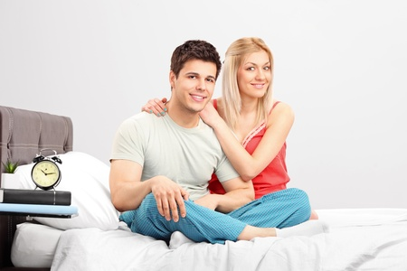 A lovely couple in pijamas sitting on a bed Stock Photo - 13227413
