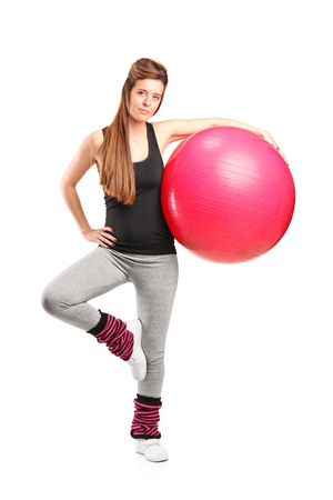 Full length portrait of a smiling female holding a fitness ball isolated on white background photo