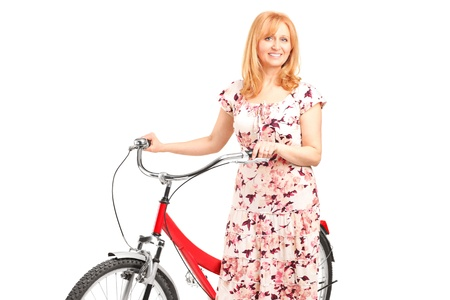 A portrait of a mature female posing next to a bicycle isolated on white background photo