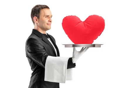 A portrait of a waiter holding a tray with a red heart shape on it isolated on white background photo