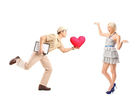Delivery boy in a rush delivering red heart shaped object and excited woman isolated on white background photo