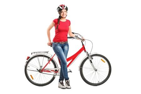 ciclista: Retrato de cuerpo entero de una mujer sonriente posando junto a una bicicleta sobre fondo blanco