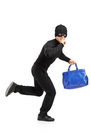 Full length portrait of a thief running with a stolen purse and finger on lips gesturing silence isolated on white background Stock Photo - 13293637