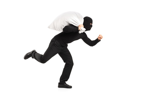 Thief carrying a bag and running away isolated on white background photo