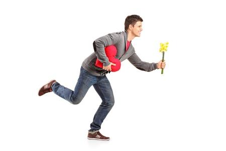 Junger Mann läuft mit einem Blumenstrauß und roten Herzen Form Objekt in seine Hände auf weißem Hintergrund