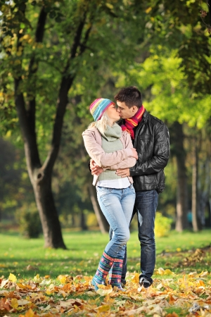 A loving couple kissing in the park in autumn photo