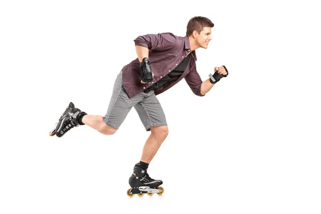 ni�o en patines: Longitud total de retrato de un hombre sobre rodillos aisladas sobre fondo blanco Foto de archivo