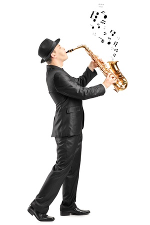 full length portrait: Full length portrait of a male playing on saxophone and notes coming out isolated against background Stock Photo