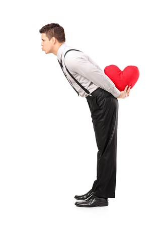 Full length portrait of a man holding a red heart shape object and giving kisses isolated on white background photo