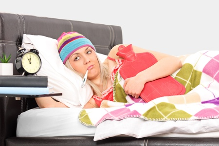 grippe: Ill woman in a bed holding a hot-water bottle and a thermometer in her mouth Stock Photo