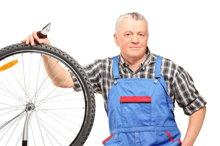 Middle aged male holding pliers and repairing bicycle wheel isolated on white background photo