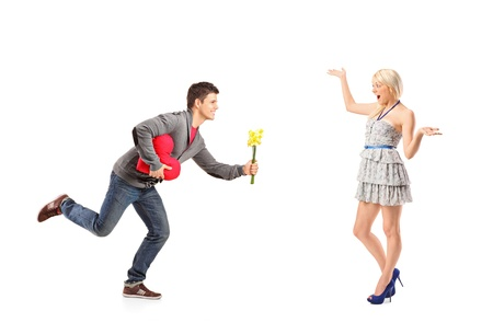 A boyfriend in love running with flowers and heart shape object towards his excited girlfriend isolated on white background Stock Photo - 13526019