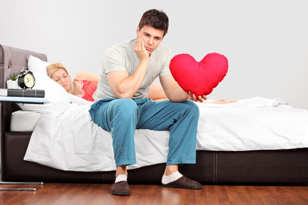 impotence: Young man in thoughts holding a heart shaped pillow while his girlfriend fall asleep