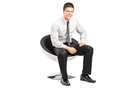 sitting on: A young handsome male sitting on chair and posing isolated on white background