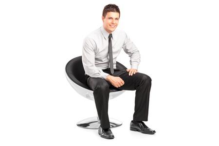 hombre sentado: Un hombre joven y guapo sentado en la silla y posando sobre fondo blanco