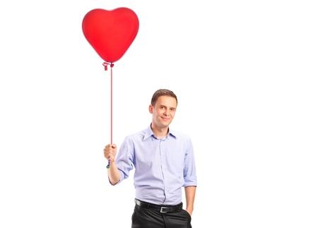 A smiling young male holding a red heart shaped balloon isolated on white background photo