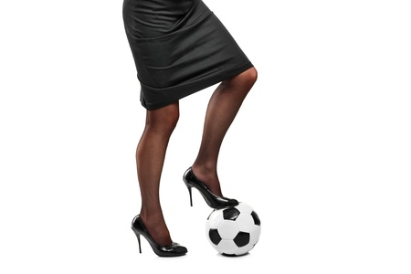 Woman in high heels standing on a soccer ball isolated on white background Stock Photo - 13612829