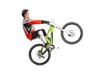Young biker with his mountain bike jumping isolated on white background photo
