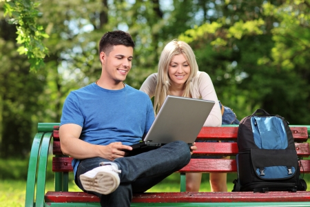 A loving couple working on a laptop in a city park Stock Photo - 13612880