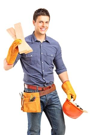 Ein lächelnder manuelle Zimmermann hält einen Helm und Schweller isoliert auf weißem Hintergrund