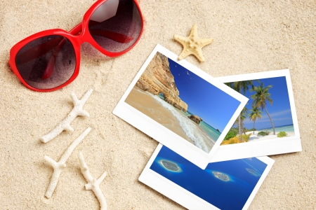 A sunglasses, few photos, starfish and corals on a sandy beach photo