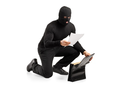 villain: A thief reading a confidential documents after stealing a briefcase isolated on white background