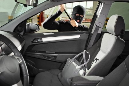 robo de autos: Un ladrón con una máscara de robo a mano tratando de robar una bolsa de cartera en un automóvil Foto de archivo