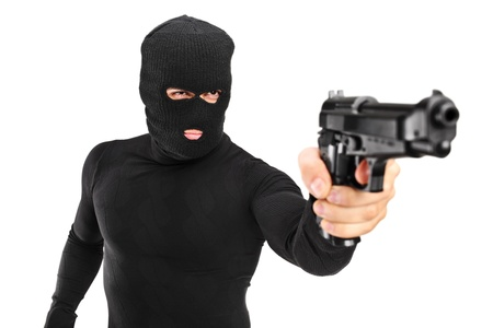 A view of a man with robbery mask holding a gun isolated against white background photo