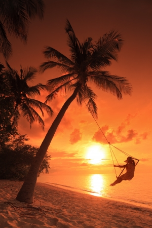 A woman relaxing on a teeter with sunset in a background in Maldives island photo