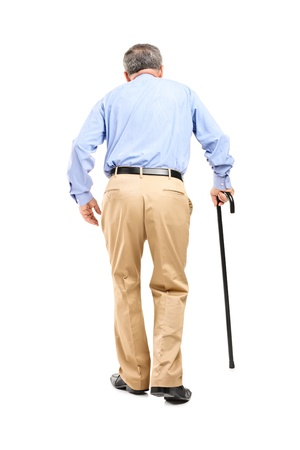 Full length portrait of a senior man with cane walking isolated on white background