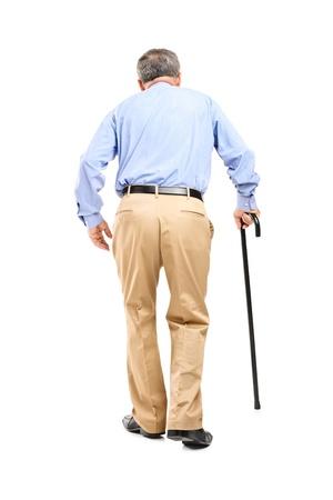 In voller Länge Portrait eines älteren Mannes mit Gehstock laufen isoliert auf weißem Hintergrund