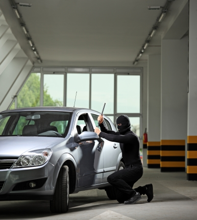 robo de autos: Un ladrón con máscara de robo a mano tratando de robar un automóvil estacionado en un estacionamiento