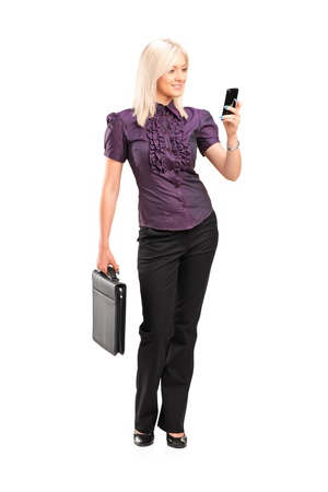 mobile phone adult: Full length portrait of a stylish young woman holding a breifcase and  talking on a mobile phone isolated on white background Stock Photo