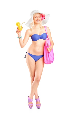 Full length portrait of an attractive blond woman in swimsuit drinking a cocktail isolated on white background photo