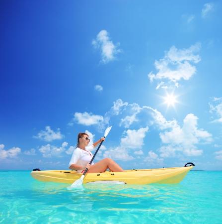 晴れた日、クレドゥ モルディブ、島 Lhaviyani 環礁にカヤックの女性