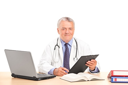 male doctor: A mature doctor posing in his office isolated on white background Stock Photo