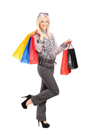 Full length portrait of a blond female posing with shopping bags isolated against white background Stock Photo - 13924381