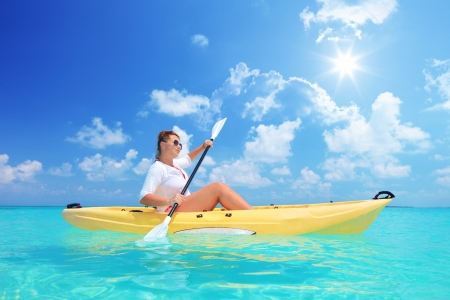 A female kayaking on a sunny day, Kuredu island, Maldives, Lhaviyani atoll photo
