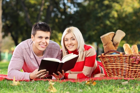 A loving couple reading a book during a picnic in city park photo
