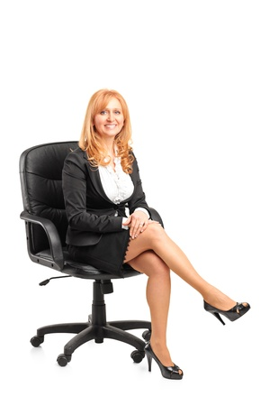 woman sitting with laptop: A portrait of a smiling  businesswoman sitting on a chair isolated on white background