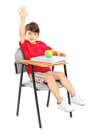 A studio shot of a schoolboy seated in a chair raising his hand isolated on white background Stock Photo - 13991273