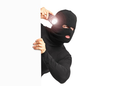 A thief with robbery mask holding a flashlight behind a white panel isolated on white background photo