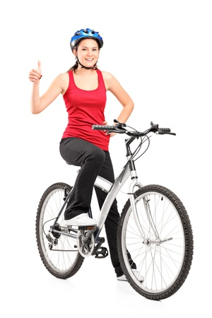 Full length portrait of a female bicyclist posing on a bicycle and giving a thumb up isolated against white background photo