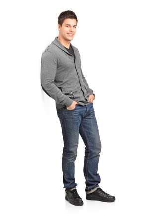 happy young man: Full length portrait of a smiling male leaning against wall isolated on white background Stock Photo