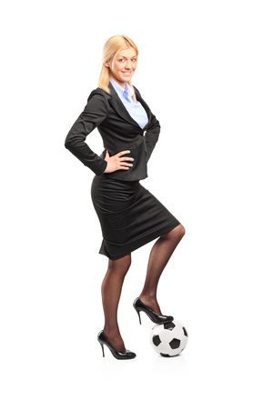 Full length portrait of a woman in high heels standing on a soccer ball isolated on white background photo